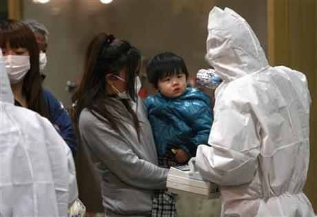 In this March 15, 2011 file photo, a child is screened for radiation exposure at a testing center in Koriyama city, Fukushima Prefecture, northeast of Tokyo, after a nuclear power plant on the coast of the prefecture was damaged by March 11 earthquake. A new study says children living near the Fukushima nuclear meltdowns have been diagnosed with thyroid cancer at a rate 20 to 50 times that of children elsewhere, a difference the authors contend undermines the government's position that more cases have been discovered in the area only because of stringent monitoring. Most of the 370,000 children in Fukushima have been given ultrasound checkups since the March 2011 meltdowns at the tsunami-ravaged Fukushima Dai-ichi nuclear plant. Thyroid cancer has been diagnosed in 137 of those children, though more broadly the disease occurs in only about one or two of every million children. (AP Photo/Wally Santana, File)